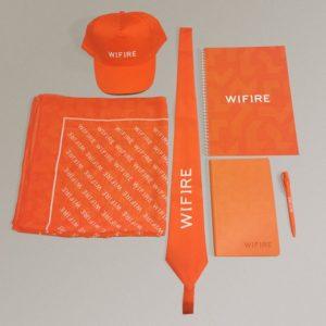 Аксессуары в фирменном стиле для  Wifire: нашейный платок и галстук (сублимационная печать), бейсболка с логотипом (шелкотрансфер), блокнот (офсет), записная книжка (блинтовое тиснение), ручка (тампопечать)